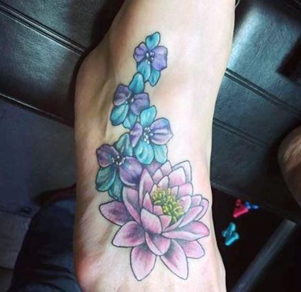 Larkspur Flowers With Lotus Tattoo On Foot